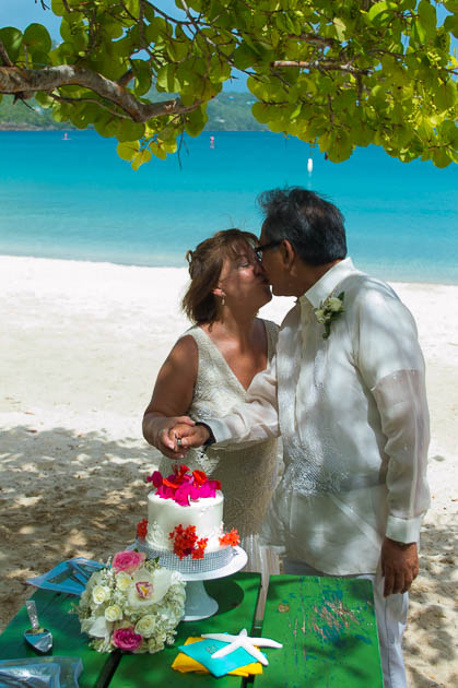 the couple cutting the cake at a beach vow renewal ceremony